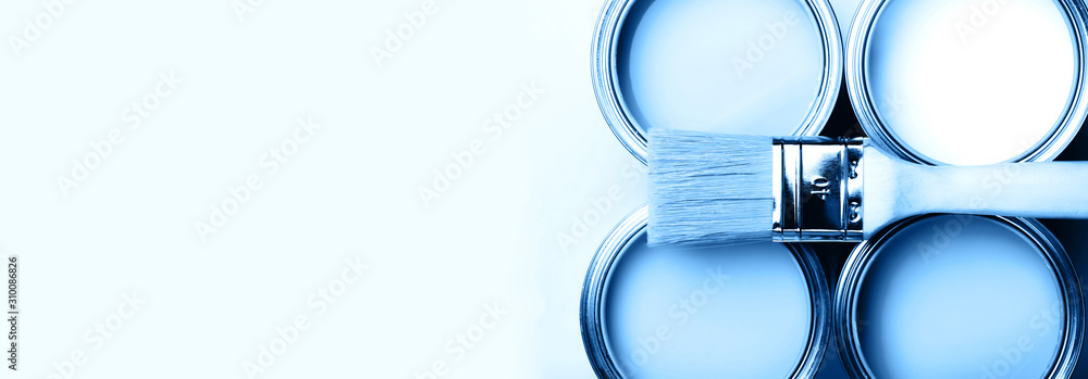 Fototapeta Brush with wooden handle on open cans on blue pastel background. Blue color. Renovation concept. Macro.
