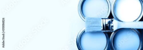 Fototapety, obrazy: Brush with wooden handle on open cans on blue pastel background. Blue color. Renovation concept. Macro.