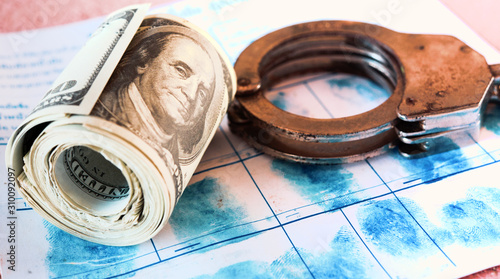 Roll of banknotes and police handcuff on fingerprint crime page file Canvas Print