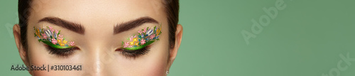 Eye makeup girl with a flowers. Spring makeup. Beauty fashion. Eyelashes. Cos...