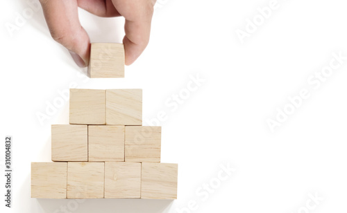 Fototapeta Hand arranging wood block stacking on top pyramid with white background