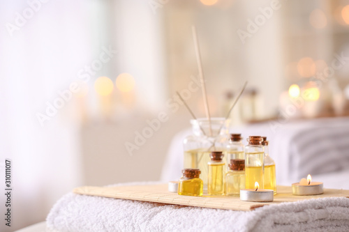 Essential oil with glowing candles and reed diffuser on table in spa salon Wallpaper Mural