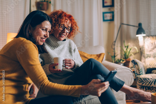 Fotografie, Obraz woman friends sitting sofa at home talking, using mobile phone,