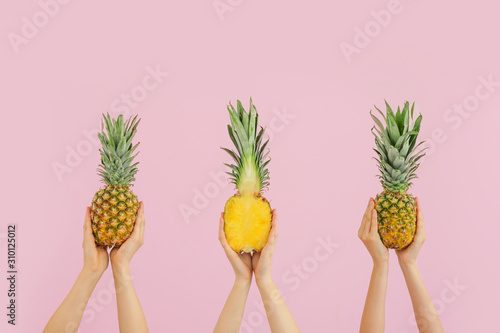 Hands with juicy pineapples on color background