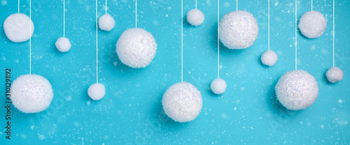 Obraz Christmas composition. The concept of a winter festive background, snowfall from white balls on a blue background. Christmas, winter, new year concept. Banner Minimalism flat lay - fototapety do salonu