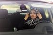 muslim young woman straightens headscarf in car