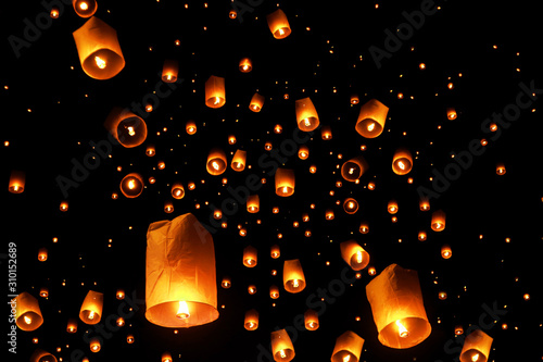 Fotografie, Obraz  swarms of sky floating lanterns are launched into the air during New year's eve and Yee Peng lantern festival traditional at Chiang Mai , Thailand