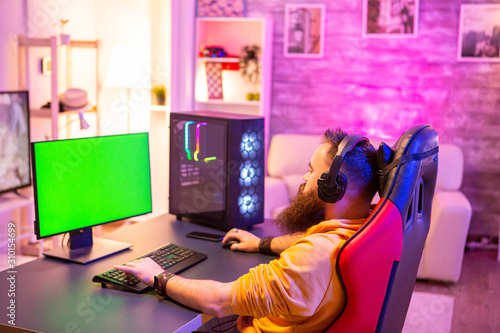 Fotografia Man playing on powerfull gaming pc in a room with neon lights on a green screen