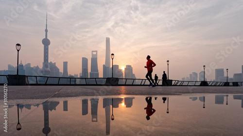 Photo Silhouette morning runner running at famous bund zone with sun rising shanghai city background