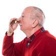 Senior man holding her nose because of a bad smell isolated on white