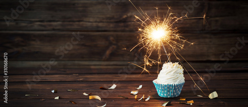 Photo birthday cake with sparkler on old wooden background
