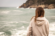 Young Woman With Sweatshirt Sitting In Front Of The Sea Looking Towards The Horizon. There Is A Mountain In The Background While Breaking A Wave In Front Of The Woman.