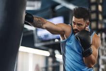 Sporty Guy Punching Boxing Bag...