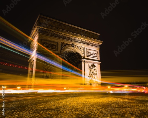 Photo Timelapse shot of light trails around Arc de Triomphe in Paris, France