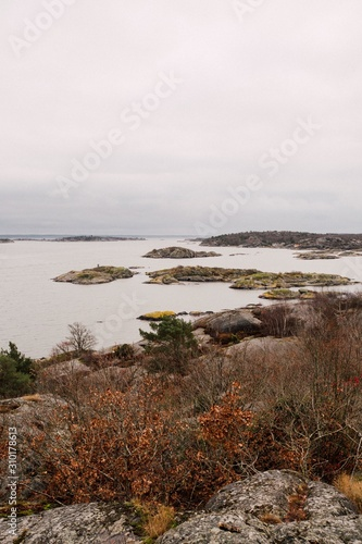 Vertical shot of the sea with ricks and surrounded by hills under a cloudy sky Canvas-taulu
