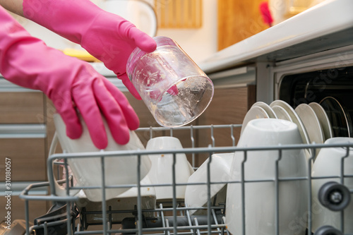 Valokuvatapetti housewife putting dirty dishware in dishwasher rack at home kitchen