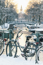Snow View Of A Dutch Canal With Bicycles In The Historic City Of Amsterdam