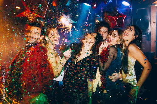 Obraz Group of friends at club having fun. New year's party with confetti and sparklers  - fototapety do salonu