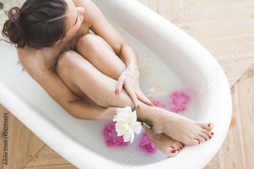 Perfect woman bathing with flowers and milk Fotobehang