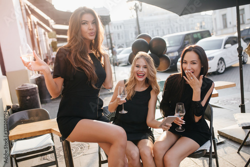 obraz PCV Outdoor portrait of confident female model in short dress sitting on table in cafe. Good-looking european woman celebrating birthday with sisters and drinking wine on city background.