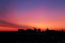Sunrise Over The City, Scenic View With Night Lights. Pink-blue Sky And Cirrus Clouds In Soft Colors Above Black Silhouettes Of High-rise Buildings, Colorful Cityscape For Background