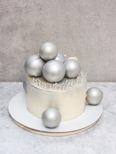 White Elegant Cake With Silver Chocolate Balls And Sprinkles.