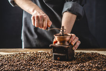 Hands Baristas In A Dark Apron Grind On A Manual Grinder Fragrant Coffee Beans. Selection Of Fresh Coffee For Espresso