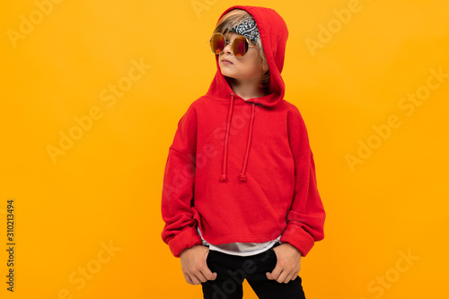 Fototapeta attractive boy with a bandana on his head in a red hoodie and glasses posing on an yellow background obraz