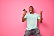 Handsome Excited Young Black Man Feeling Excited While Viewing Content On His Smartphone, Celebrating Winning