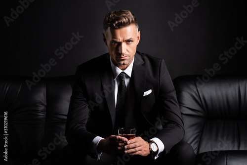 Handsome businessman with glass of whiskey looking at camera on couch isolated o Billede på lærred