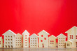 Leinwanddruck Bild - Miniature wooden houses on a red background. Real estate concept. City. Agglomeration and urbanization. Market Analytics. Demand for housing. Rising and falling home prices. Population. Copy space