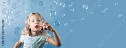 Stampa su Tela Cute girl with curly hair blowing bubbles on blue background