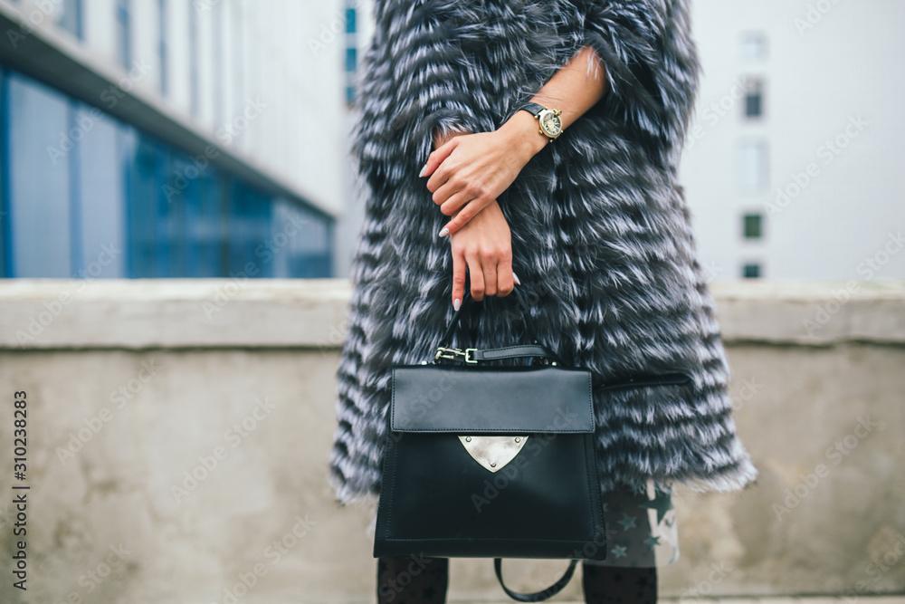 Fototapeta stylish woman in winter fur coat walking in street