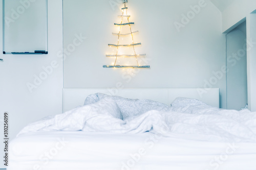 Fotografie, Obraz  Unusual Christmas tree made of wooden sticks with a garland on the white wall above the bed
