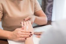 Masseur Rubs Cream In The Hands Of A Young Beautiful Brunette Patient, Doing Massage. Close-up. In A Beauty Salon. Against A Calm Background, In Warm Colors