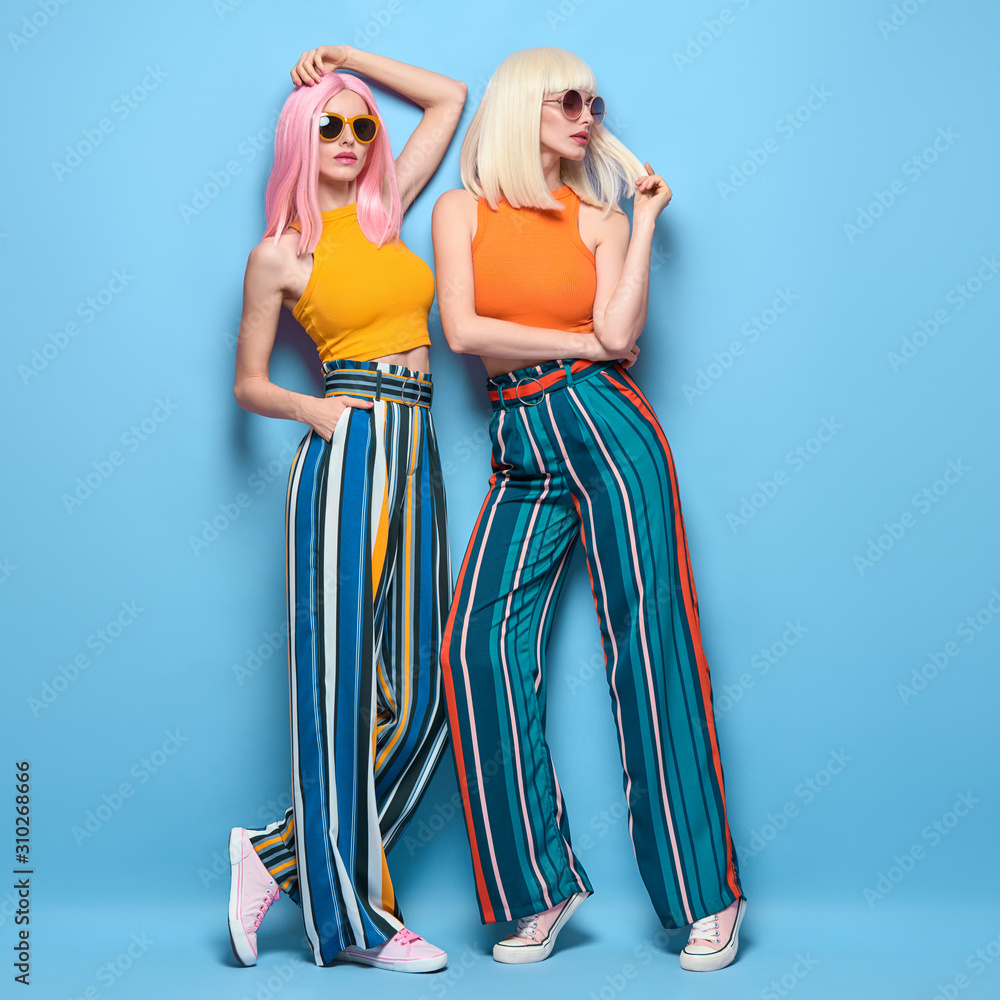 Fototapeta Two fashionable girl posing in Studio. Beautiful Adorable young woman in Stylish summer colorful outfit, Trendy dyed hair, make up. Glamour model sister friend, fashion concept on blue, full-length