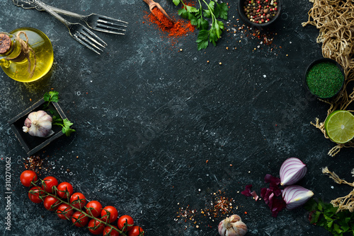 obraz dibond Food banner. Spices, vegetables and herbs on a black stone background. Top view. free space for your text. Rustic style.
