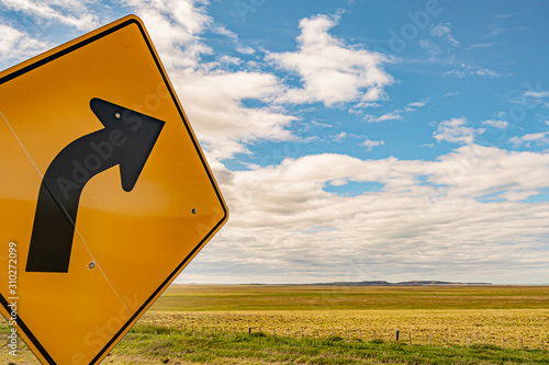 right turn sign with a green field in the background and sky with clouds Canvas Print