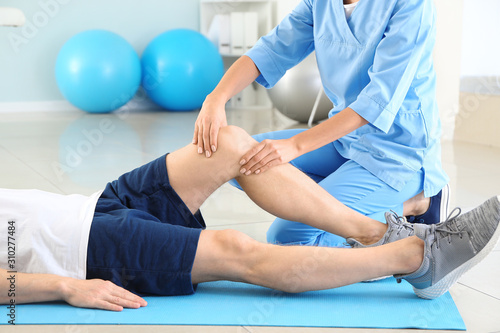 Physiotherapist working with male patient in rehabilitation center