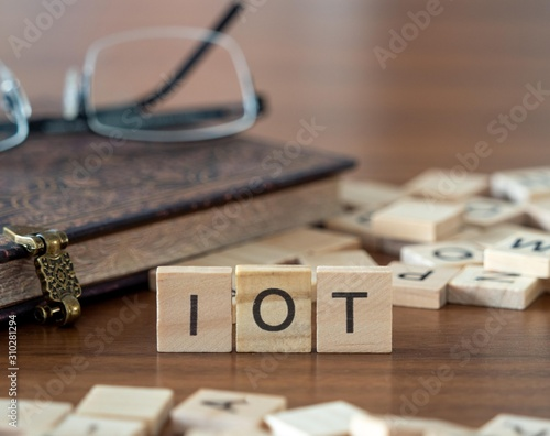the acronym iot for Internet of Things concept represented by wooden letter tile Canvas Print