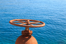 Handwheel Of A Rusty Valve Regulating The Flow Of A Fluid Through A Pipe By Crystal Clear Sea Water. Blue Rippled Surface In The Background On A Sunny Day. Water Supply, Sewage, Gas, Oil Installation