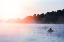 Fisherman On The River In The Fog In The Park On The Nature