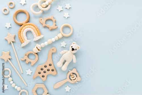 Cute wooden baby toys on light-blue background. Knitted bear, rainbow, dinosaur toy, beads and stars. Eco accessories, beanbag and teethers for newborn. Blank space for text. Flat lay, top view