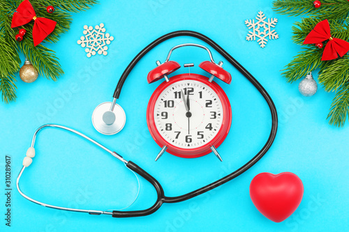 Branches of spruce, christmas toys, red heart with stethoscope and alarm clock with five minutes to twelve o'clock on a blue background Wallpaper Mural