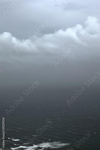 Photo Overcast, heavy sky looming over a dark, agitated sea.