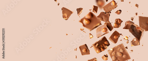 Fotografía  Flying in the air broken bar of milk chocolate with nuts and flakes on pastel pink background