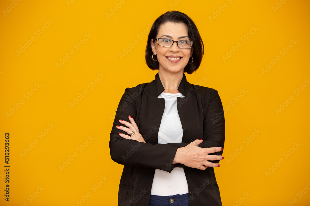 Fototapeta Attractive middle aged woman with beautiful smile on yellow wall. Pretty older business woman, successful confidence with arms crossed.