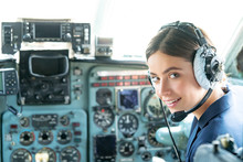 Happy And Successful Flight. Smiling Female Pilot In The Aircraft , She Is Holding Aviator Headset And Looking At Camera. Wishes A Successful Fligh.