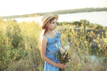 Little Girl In A Straw Hat With A Bouquet Of Wildflowers On A Background Of A Beautiful Landscape