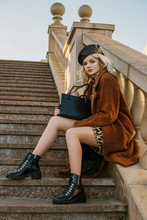 Outdoor Full-length Fashion Portrait Of Young Elegant Woman Wearing Trendy Brown Faux Fur Coat, Leather Beret, Lace Up Ankle Boots, Holding Classic Handbag, Sitting, Posing On Stairs, In Street